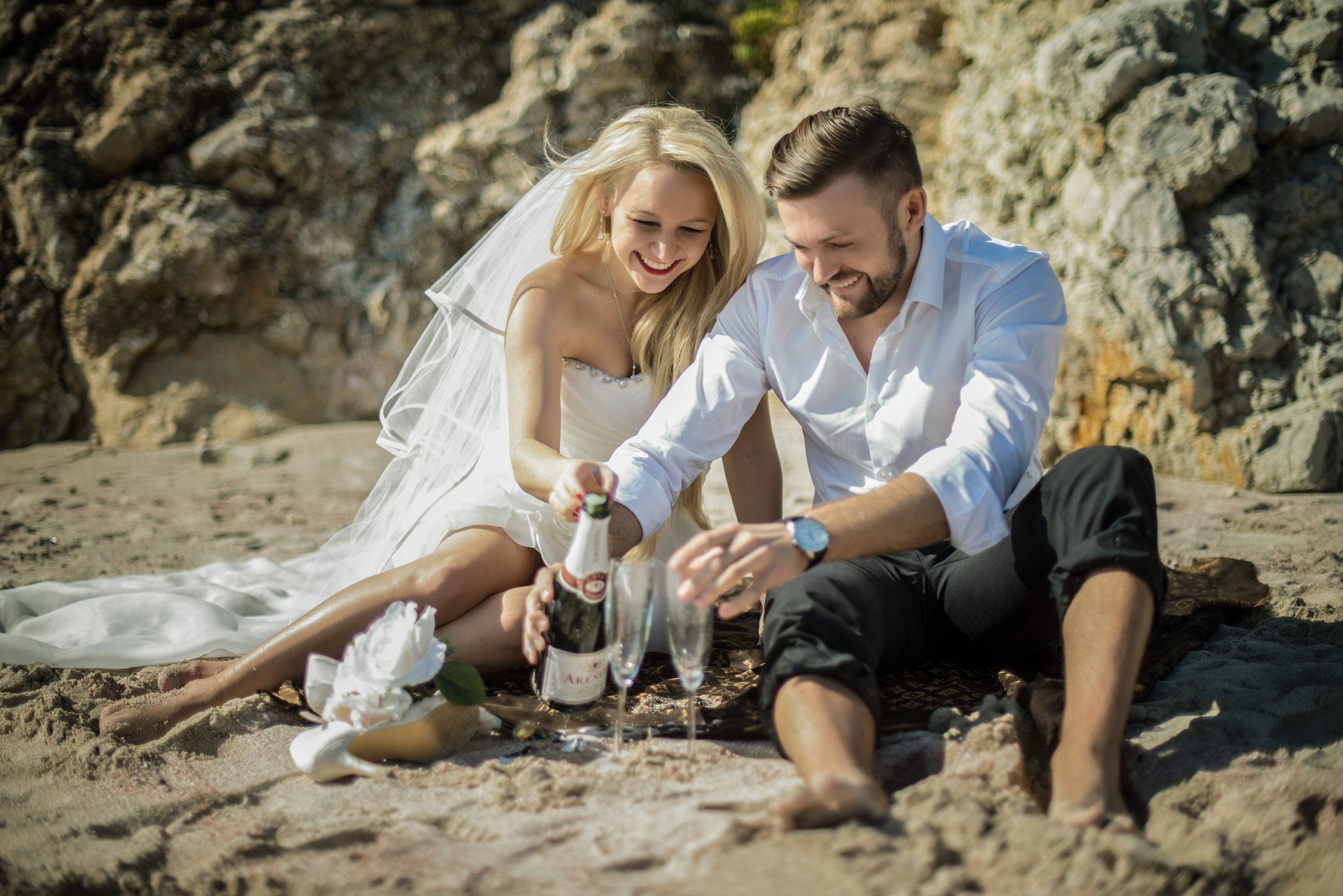 Brautpaar am Strand mit Sekt während eines Hochzeitsvideo drehs.