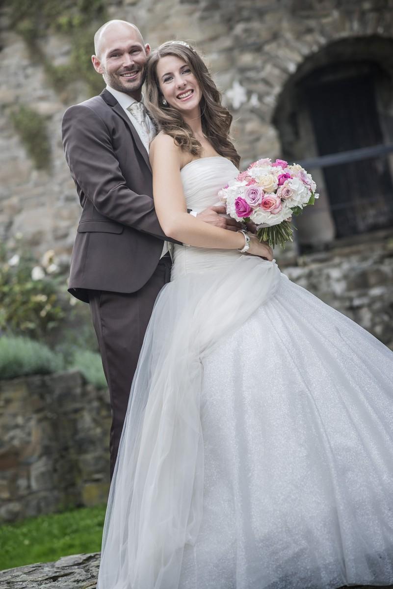 Brautpaar posiert vor Burg in die Kamera. hochzeitsvideo hochzeit filmen lassn hochzeitsvideo koeln