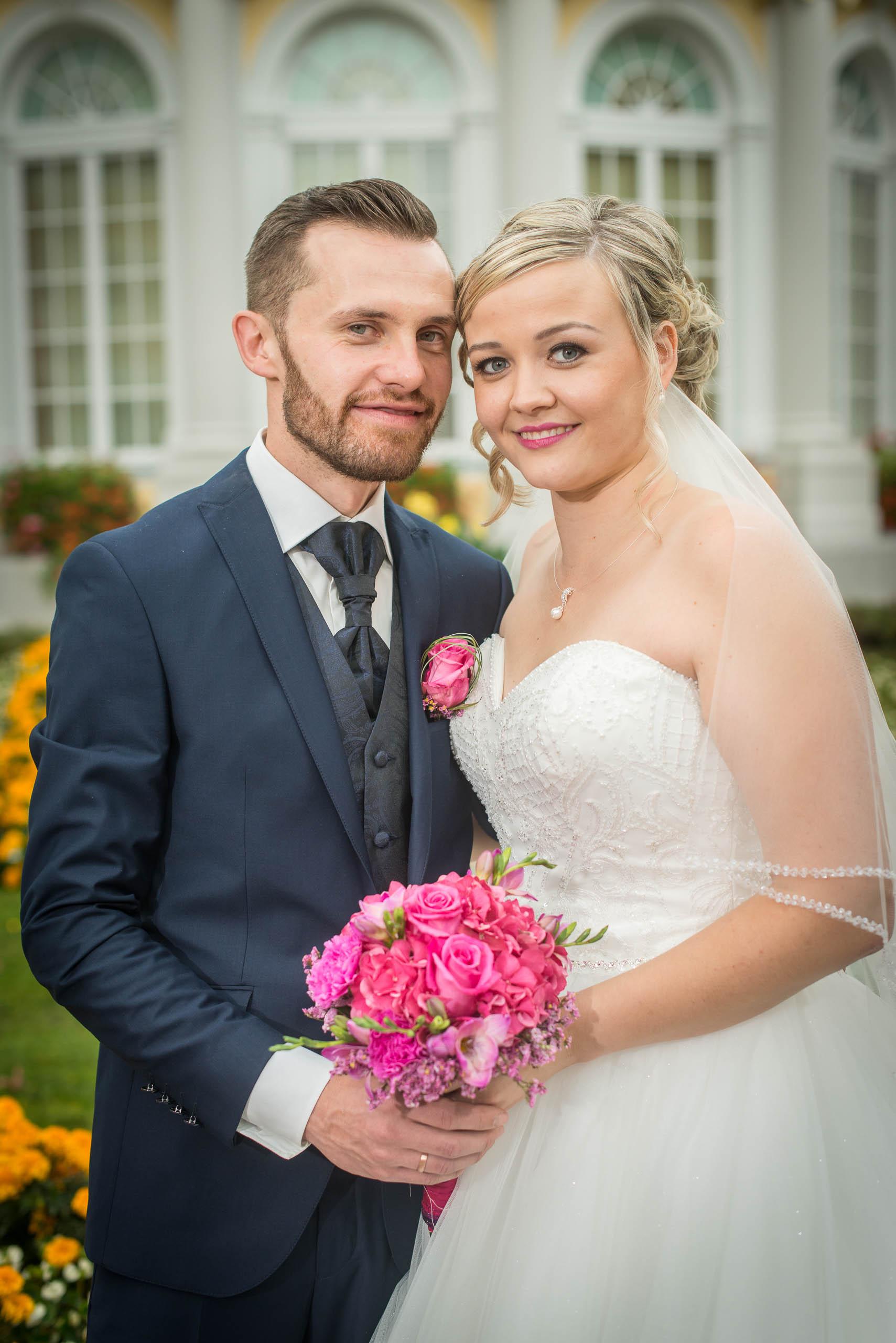 hochzeitsvideo hochzeit filmen lassn hochzeitsvideo koeln Brautpaar lächelt in die Kamera und steht im Schlossgarten.
