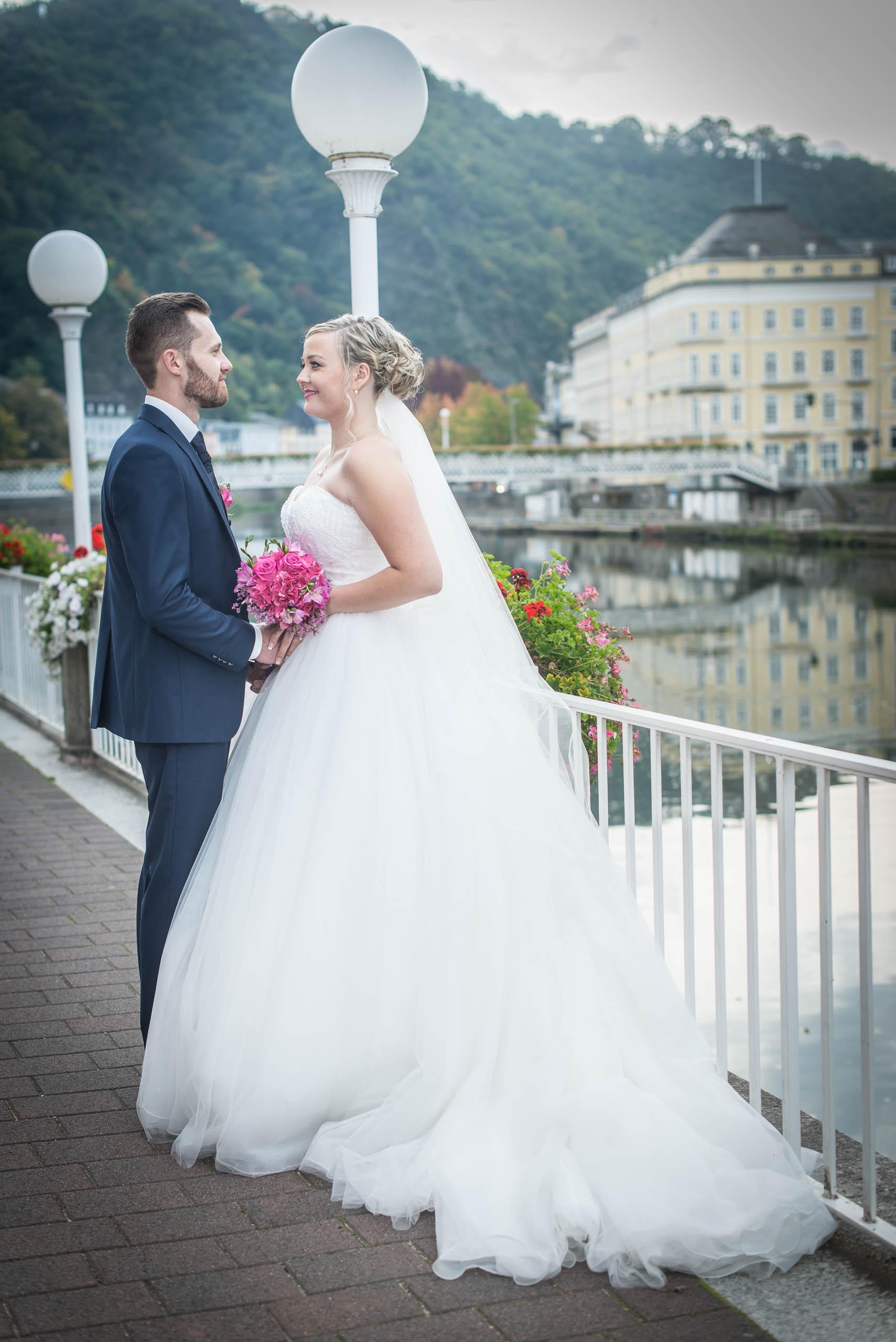 Brautpaar posiert am Brückengeländer und schauen sich gegenseitig an hochzeitsvideo hochzeit filmen lassn hochzeitsvideo koeln hochzeitsvideo