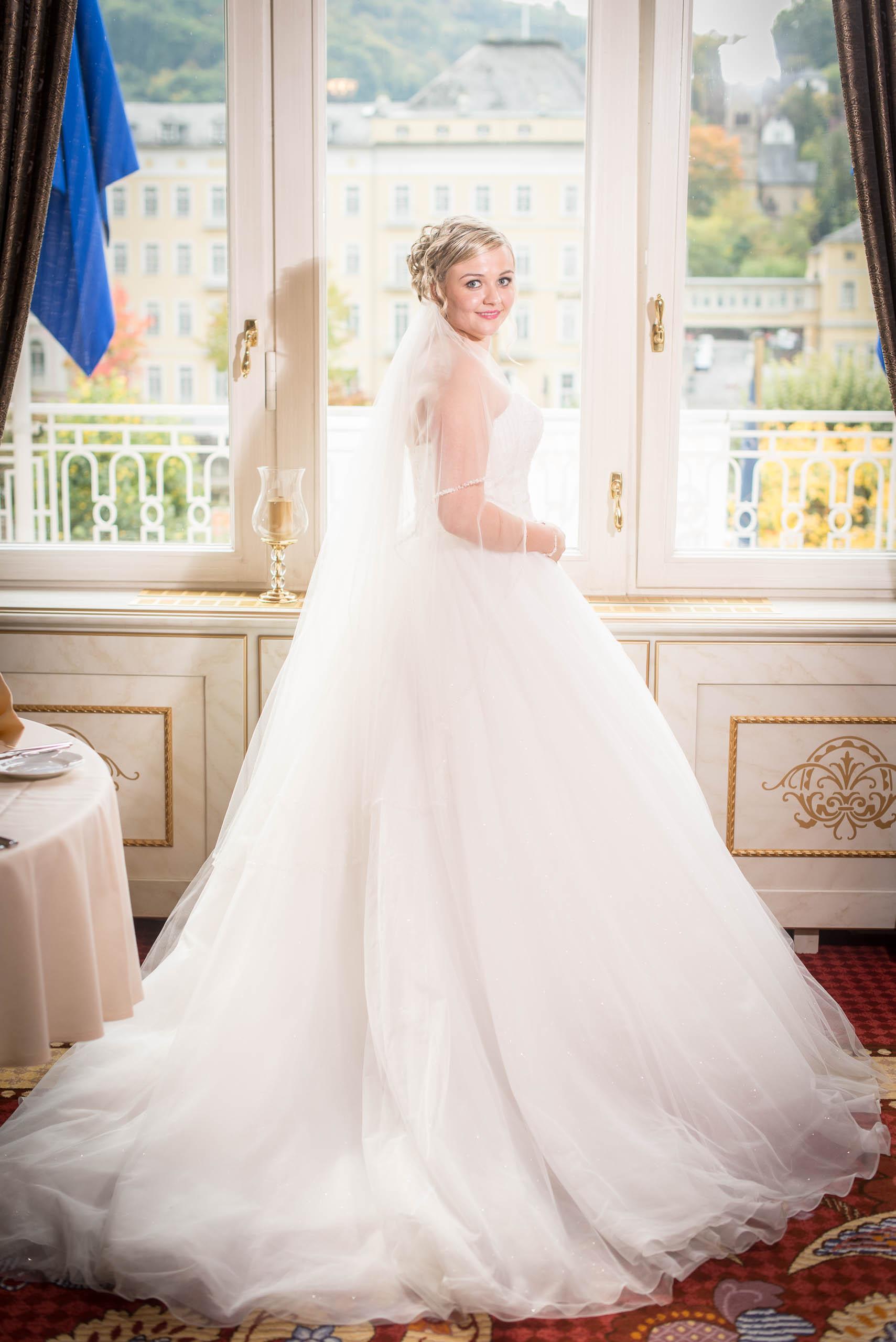 Braut lächelt in die Kamera. Nach dem Getting ready. Steht am Fenster. hochzeitsvideo hochzeit filmen lassen hochzeitsvideo koeln
