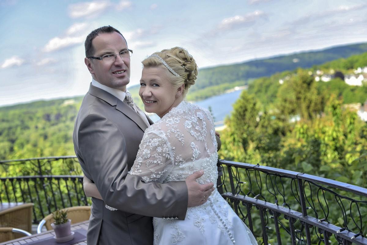 Brautpaar auf Brücke posiert in die kamera und im hintergrund ist ein wald und ein see hochzeitsvideo hochzeitsfilm hochzeitsvideo koeln hochzeitsvideografie