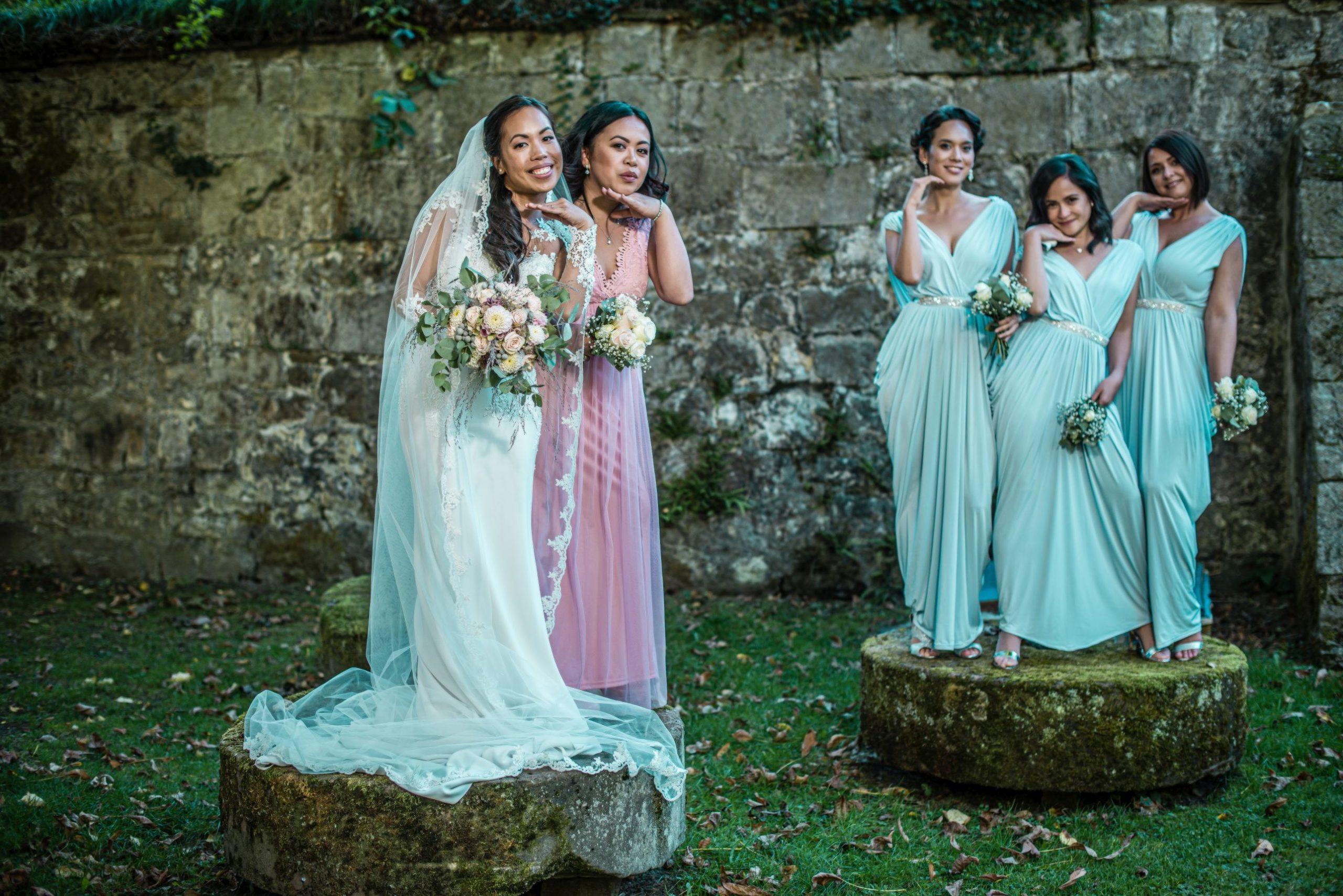Braut posiert mit Trauzeugin und steht auf einem moosbedeckten Stein hochzeitsvideo hochzeitsvideograf
