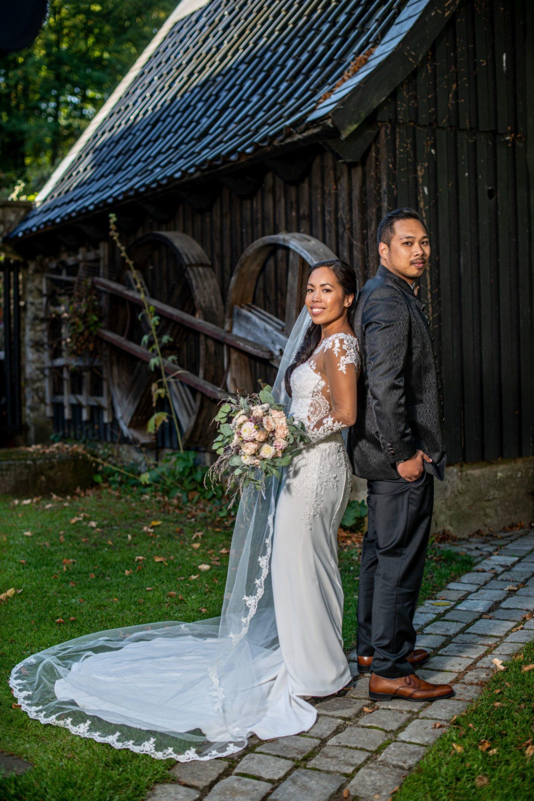 brautpaar steht vor einer scheune und lächelt in die kamera hochzeitsvideo hochzeitsvideograf hochzeitsfoto