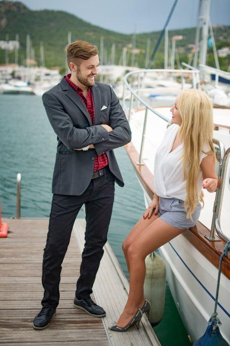 brautpaar posiert am yachthafen und lächeln sich gegenseitig an hochzeits video hochzeitsvideograf